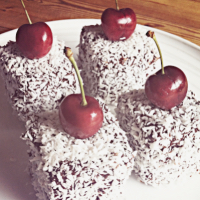 Four cherry Lamington sponge cakes, covered in ganache and dessicated coconut with a cherry decoration