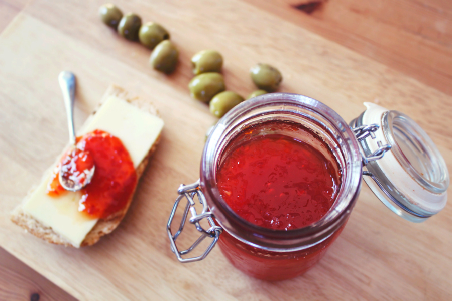A pot of homemade soft set chilli jam shown served on granary bread with cheddar and olives