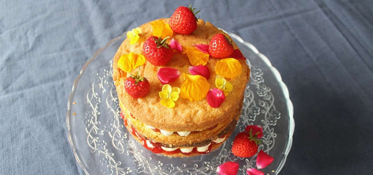 Four layered strawberry shortcake made with polenta and ground almonds, with chantilly cream, jam, strawberries, chocolate spread and edible flowers